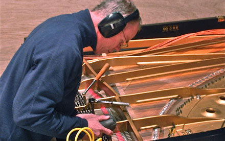 Photo of Keith Akins, RPT, restringing a Baldwin SD-10 concert grand on location in Menominee Michigan